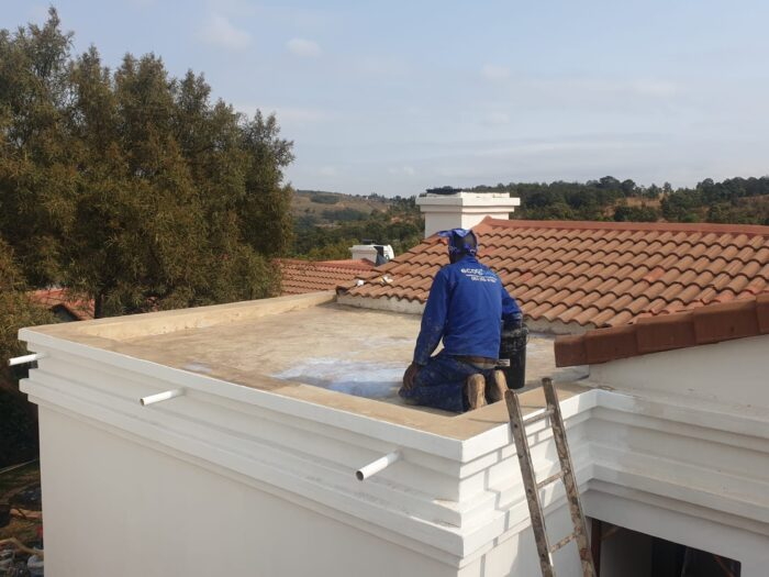 Concrete roof slab being primed for waterproofing